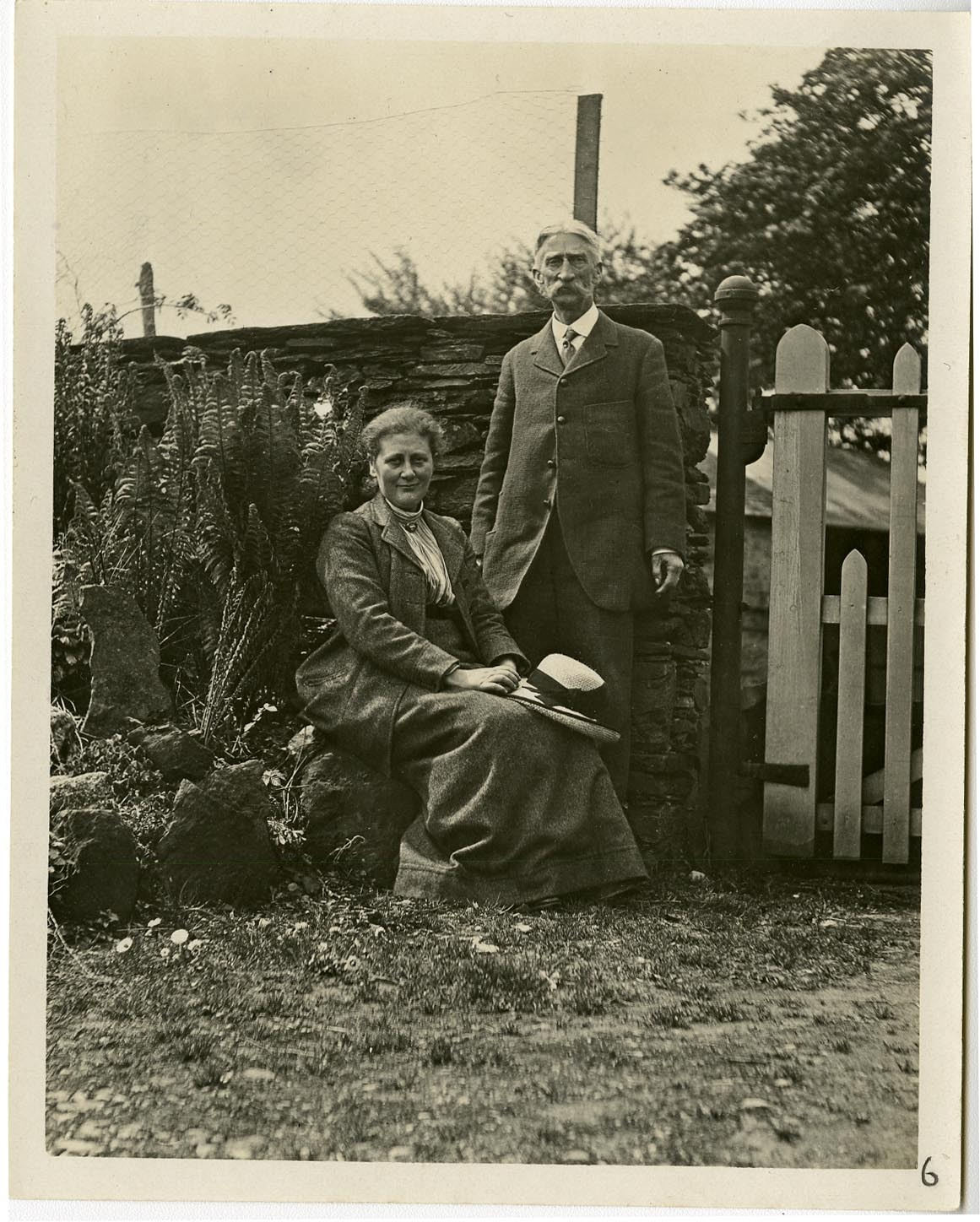 Beatrix seated with C.Y. King standing in her garden at Hill Top, near Sawrey